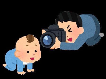 大きな一眼レフカメラを構えて赤ちゃんの写真を撮影しているお父さん